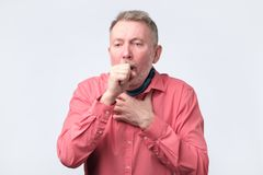 European gentleman in red shirt coughing because of pulmonary diseas royalty free stock photo