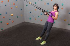 European girl athlete pulling herself up on gymnastics ribbons. Against the wall for climbing. stock photos