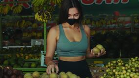 European girl in a black protective mask buys organic fruits in a store
