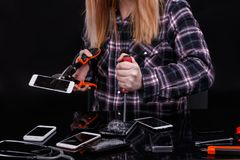 A girl, breaks smartphones with construction tools. On a black background. Close-up. stock images