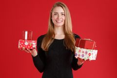 European girl holding Christmas gift boxes and smiling. On a red background. royalty free stock image
