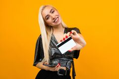 European Girl Holds A Phone And A Credit Card With A Mockup On A Yellow Studio Background Stock Photos