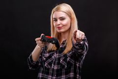 European girl, holds a joystickand clenched her lips showing in front of her index finger. stock image