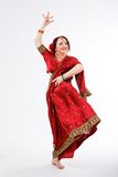 European girl in red indian saree. European brunette girl in red indian saree dancing with her hands and flying skirt in studio on gray background Royalty Free Stock Photos