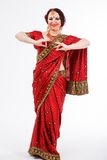 European girl in red indian saree. European brunette girl in red indian saree dancing with her hands in studio on gray background Royalty Free Stock Images