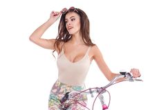 The European girl, sits on a bicycle, looks away and adjusts the sunglasses on her head. Isolated. stock images