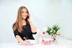 beautiful European girl takes a call on the phone and writes in a notebook on a white background. Nearby are flowers and stock photography