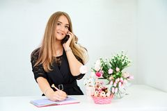 beautiful European girl takes a call on the phone and writes in a notebook on a white background. Nearby are flowers and royalty free stock images
