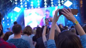 European girl takes a photo video shooting panoramic view look of the concert front of the stage phone technology. European girl takes a photo video shooting stock footage