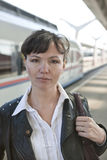 The European girl and train. The girl, the brunette in a white blouse and a leather jacket. Against a departing train, at station. Girl  take a train Stock Photos