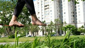 European girl is walking on a tight line in a city park. Woman balancing on slackline, close-up royalty free stock photos