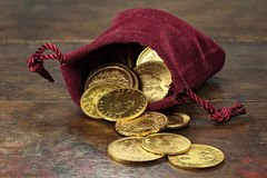 European gold coins. Various European circulation gold coins from the 19th/20th century in a velvet purse on rustic wooden background Royalty Free Stock Photo