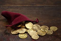 European gold coins. Various European circulation gold coins from the 19th/20th century in a velvet purse on rustic wooden background Royalty Free Stock Images