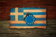 European and Greek flag concept. European flag behind burnt Greek flag grunge background Stock Image