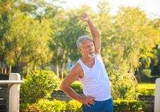 Grey Bearded Old Man in White Vest Bends Body in Park. European grey bearded old man in white vest blue shorts does morning exercises one hand up in tropical stock photography