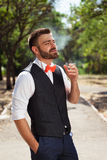European groom smokes in the park Stock Image