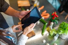 The guy and girl are standing in the kitchen and using a tablet. Close-up. The European guy and girl are standing in the kitchen and using a modern tablet that Stock Photo