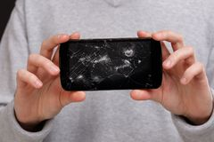 A guy in a gray jacket is holding a broken smartphone in both hands. Close-up. Royalty Free Stock Photography