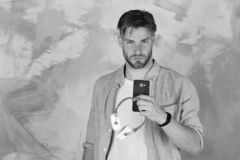 European guy have fun time. Blue eyed stylish hipster with smartphone. Cheerful teenage dj listening songs via earphones. Musical lifestyle. American handsome royalty free stock images
