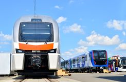 European high-speed passenger train and modern subway rolling stock and tramway on an open  railway area of the rail car assembly. Plant Stadler - Image stock image