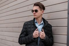 European hipster young man in a trendy plaid jacket in a vintage shirt in fashionable sunglasses with a stylish hairstyle poses. Near a wooden building on the royalty free stock photo