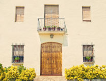 European house facade with wooden door, windows and plants Royalty Free Stock Image