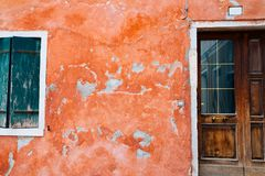 European house, Red wall and wooden door and window in Burano island, Venice, Italy. European old house, Red wall and wooden door and window in Burano island stock photos