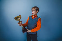 European-looking boy of ten years award cup on a. European-looking boy of ten years award cup on gray background stock images