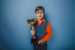 European -looking boy of ten years award cup on. A gray background royalty free stock photos