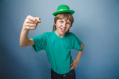 European-looking boy of ten years discontent is. Pointing at the camera, wearing a  hat on a gray  background Royalty Free Stock Photos