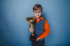 European-looking boy of ten years in glasses award. Smile, cup on a gray background royalty free stock image