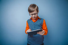 European-looking boy of ten years in glasses plays Royalty Free Stock Photo