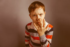 European-looking boy  of ten years licks his Stock Photos