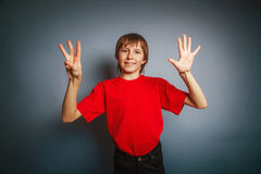 European-looking boy of ten years shows a figure Royalty Free Stock Images