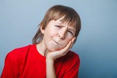 European-looking boy of ten years toothache, hand Stock Image