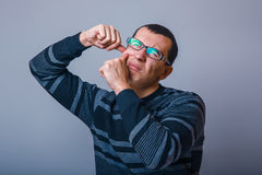 European-looking male of about thirty brunet. Squeezing a pimple on the face stock photo