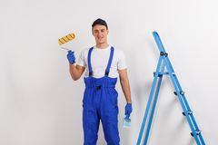 European male worker in blue uniform holds a clean construction roller and paintbrush and smiles. A handsome young European male construction worker dressed in Stock Photos