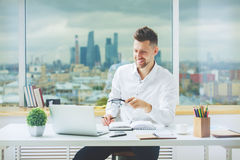 European male working on project. Handsome european male working on project at modern office desk Stock Photo