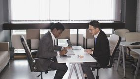 Two men sit in armchairs at the office and talking. European man and African American man sitting in armchairs and negotiate stock video footage