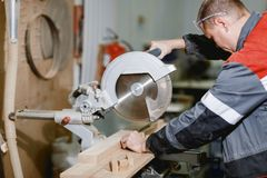 A man works with a tree near a large bar cutting machine. Close-up. stock image