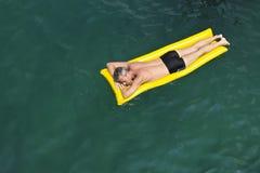 The  European man sleeping on yellow rubber mattre Royalty Free Stock Image