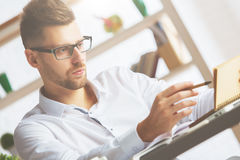 European man with spiral notepad. Portrait of young european man with spiral notepad sitting at office desk Royalty Free Stock Photo