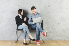 European man and woman with devices. European men and women sitting on chairs with laptop and smartphone in hands. Interior with wooden floor and concrete wall Stock Photos