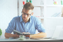 European man writing in organizer. Portrait of handsome european man at workplace writing in hardcover organizer Royalty Free Stock Photography
