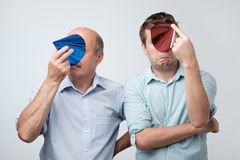 mature father and son hiding their face with birthday cap after great party having hangover stock photo