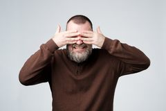 European mature man covering his face by hands royalty free stock images