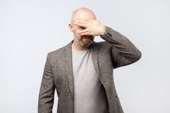 European mature man covering his face by hand and peeping at camera stock image