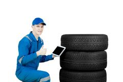 European mechanic shows thumb up near tires. European male mechanic holding a digital tablet while showing thumb up near the tires, isolated on white background Stock Photos
