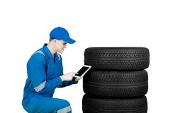 European mechanic using a tablet near the tires. European male mechanic using a digital tablet while checking tires in the studio, isolated on white background Royalty Free Stock Image