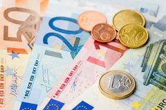 European money - one Euro coin with Euro cents and banknotes Stock Images